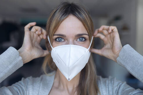 Portrait of young woman putting on protective mask - JSRF00983