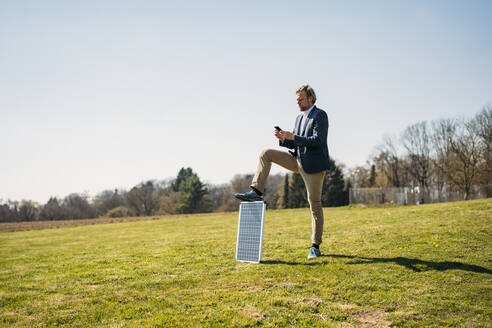 Male professional using smart phone while standing with solar panel on grass at park against clear sky during sunny day - JOSEF01445