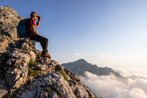 Hiker looking at view while sitting on mountain at Bergamasque Alps, Italy - MCVF00554