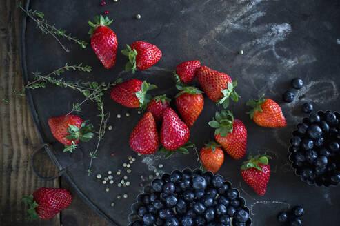 Thyme, peppercorn,blueberriesand strawberries on rustic baking sheet - ASF06665