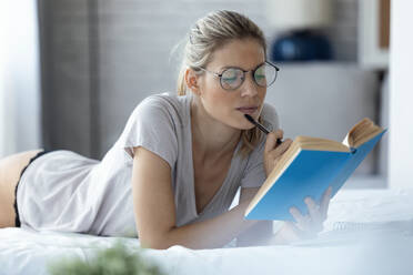Blond woman reading a book lying in bed - JSRF00996