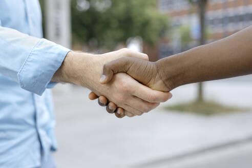 Friends shaking hands in city - KMKF01447