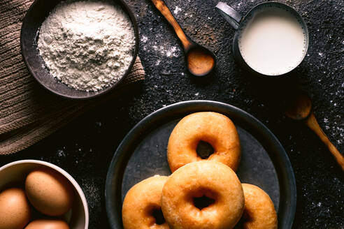Top view of fresh doughnuts placed on rough table near various pastry ingredients and utensils in kitchen - ADSF10401