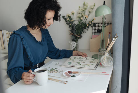 Brunette woman artist sitting at table with cup of coffee and looking at drawings in workplace - ADSF10522