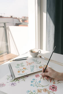 Crop person hand with brush painting watercolor flowers on large sheet at desk - ADSF10534
