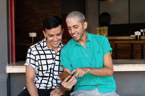 Gay man pointing while sharing mobile phone with friend while sitting restaurant counter - SPCF00830