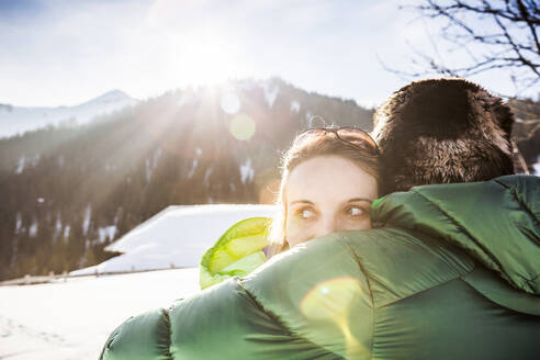 Couple cuddling in winter landscape, Achenkirch, Austria - DHEF00277