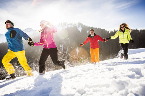 Group of carefree friends running and having fun in snow, Achenkirch, Austria - DHEF00280