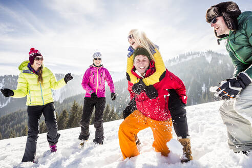 Group of carefree friends having fun in snow, Achenkirch, Austria - DHEF00301