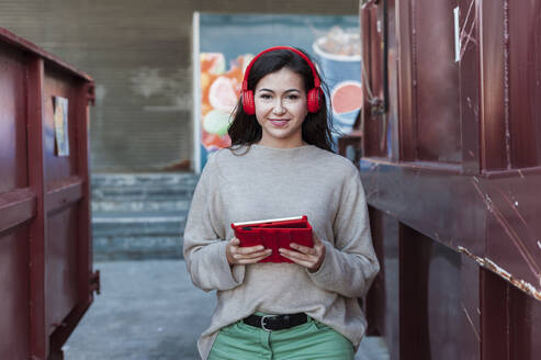 Smiling beautiful woman listening music on headphones while holding digital tablet - JMPF00319