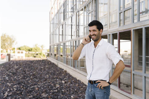 Smiling businessman talking on phone outside building - MPPF01023
