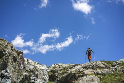 Man hiking on top of mountain at Western Rhaetian Alps, Sondrio, Italy - MCVF00567