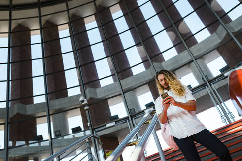 Man with long hair using phone while standing on staircase at railroad station - JMPF00333