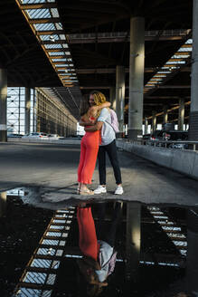Couple embracing each other with reflection on puddle in city - JMPF00342