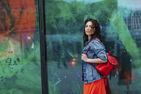 Young smiling woman at glass wall - OGF00463