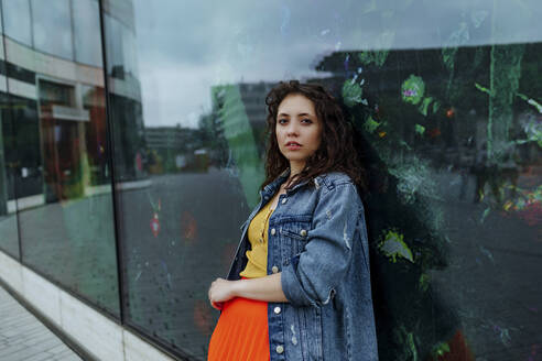 Young smiling woman leaning on glass wall - OGF00466