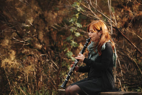Beautiful redhead female musician practicing playing clarinet while sitting on bench in forest - MRRF00270