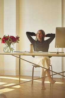 Businesswoman with hands behind head while sitting at home office - MCF01057