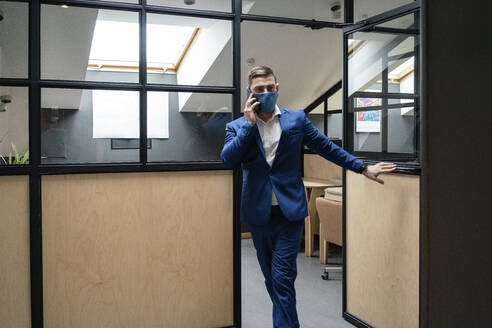 Male entrepreneur wearing protective face mask while walking out of cubicle at creative office during COVID-19 epidemic - VPIF02671