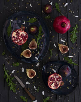 Top view of fresh cut figs and pomegranates placed on plates near arugula and knife on lumber table - ADSF10971