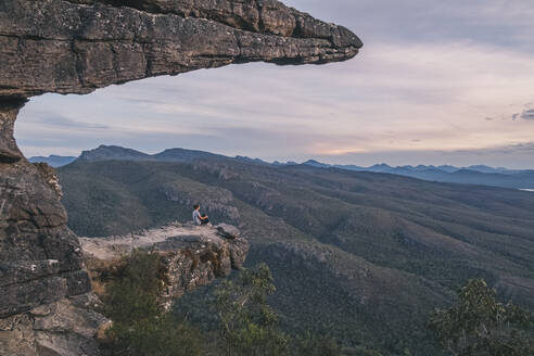 Woman sits at the Balconies and looks the landscape of the Grampians National Park, Victoria, Australia - CAVF88290