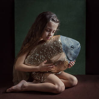 A girl with a new friend a fish is sitting with a fish in her hands - CAVF88308