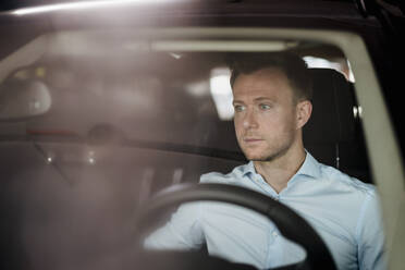 Serious male entrepreneur looking away while sitting in car - DIGF12878
