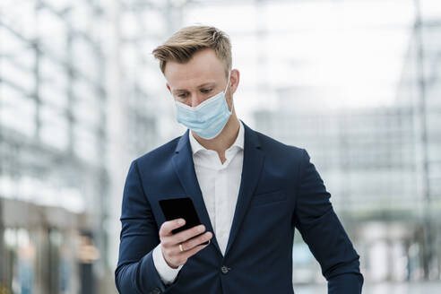 Businessman using smart phone while wearing face mask in city - DIGF12890