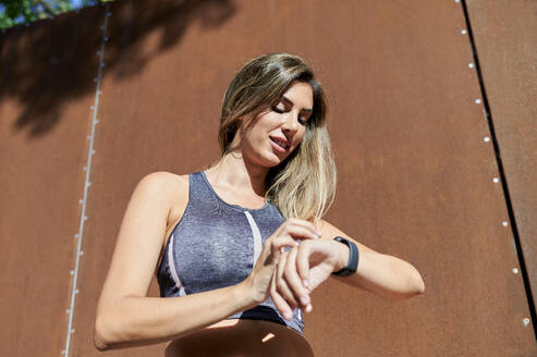 Beautiful woman checking the time against wall during sunny day - KIJF03209