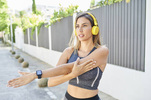 Woman listening to music while exercising outdoors - KIJF03212