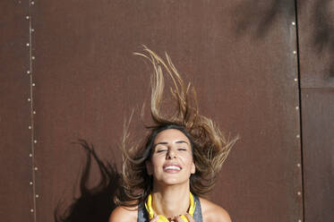 Smiling woman with headphones jumping against wall - KIJF03221
