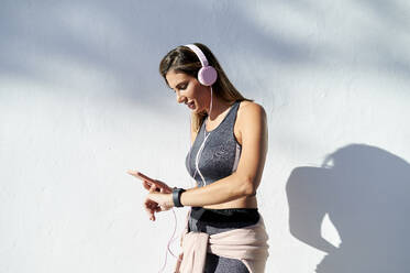 Smiling woman with headphones using phone while checking the time in city - KIJF03224