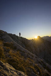 Rear view of hiker standing on viewpoint during sunrise, Gimpel, Tyrol, Austria - MALF00061