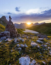 Hiker sitting on rock during sunset at Lake Rappensee, Bavaria, Germany - MALF00070