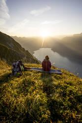 Female hiker sitting on viewpoint during sunset, Augstmatthorn, Switzerland - MALF00076