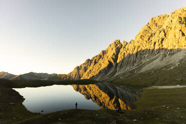 Hiker standing at Lake Kogelsee in the evening, Tyrol, Austria - MALF00121