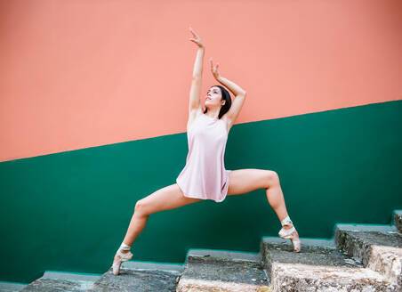 Full body young brunette ballerina in pointe shoes standing on tip of toes on weathered steps and raising arms while dancing against striped wall on street - ADSF11045