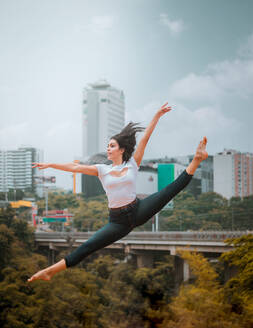 Full body energetic barefoot woman in casual clothes jumping and doing splits while dancing against contemporary city and cloudy sky - ADSF11048