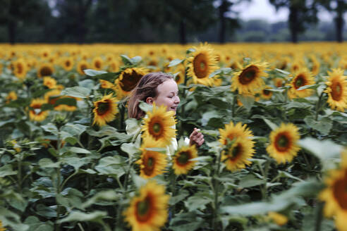 Smiling girl running in sunflower field during summer - OGF00486