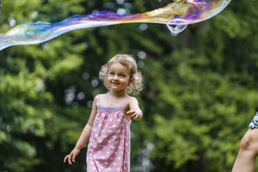 Smiling girl looking at bubble while standing at park - DIGF12911