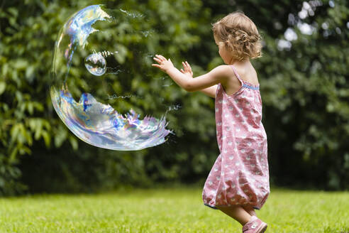 Cute girl exploding bubble at public park - DIGF12914