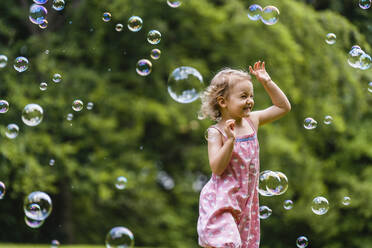 Cheerful girl running amidst bubbles at park - DIGF12917