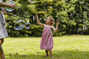 Cute girl exploding bubble with stick by brother at park - DIGF12926