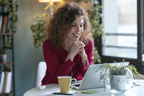 Happy businesswoman using laptop while working from home - JSRF01074