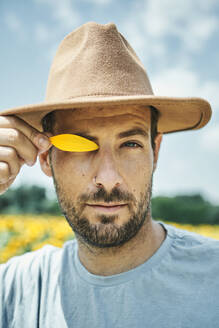 Man covering eye with yellow petal in field during summer - VEGF02714