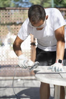 Man using circular saw while working at construction site - CJMF00333