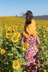 Mother carrying daughter on shoulders in sunflower field during sunny day - GEMF04086