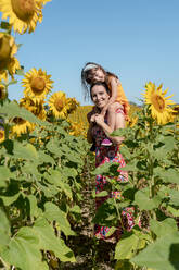 Smiling mother carrying daughter on shoulders in sunflower field - GEMF04089