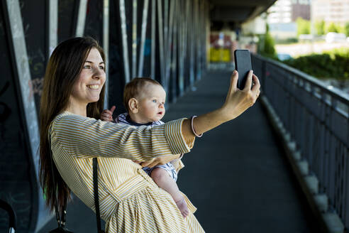 Smiling mother with her baby boy taking a selfie on bridge - IHF00387