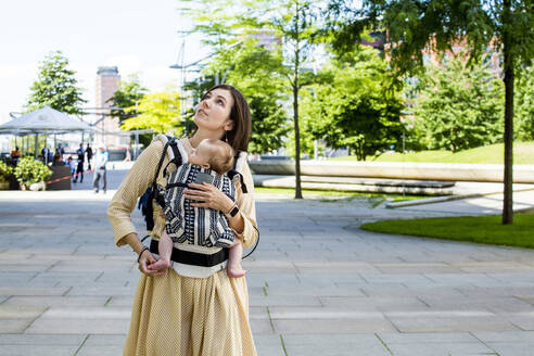 Mother with her baby boy in baby carrier in HafenCity, Hamburg, Germany - IHF00393